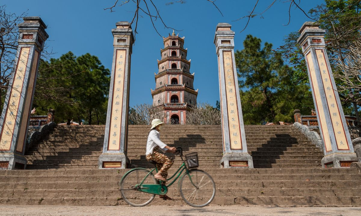 Vietnamese woman cycling through Hue (Dreamstime)