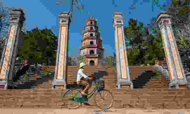 Vietnamese woman cycling through Hue (Dreamstime)