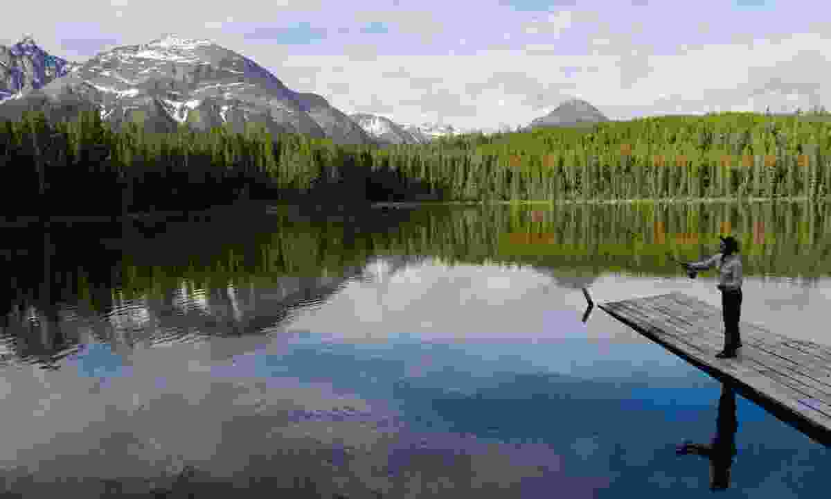 Fishing from a dock with views of the mountains at Cheshi Lake (Destination BC/Albert Normandin)