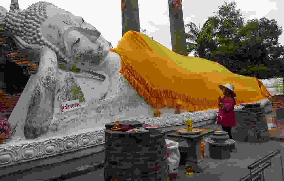 A lady worships a reclining Buddha statue in Wat Yai Chai Mongkhon (Sanghamitra Sarkar)