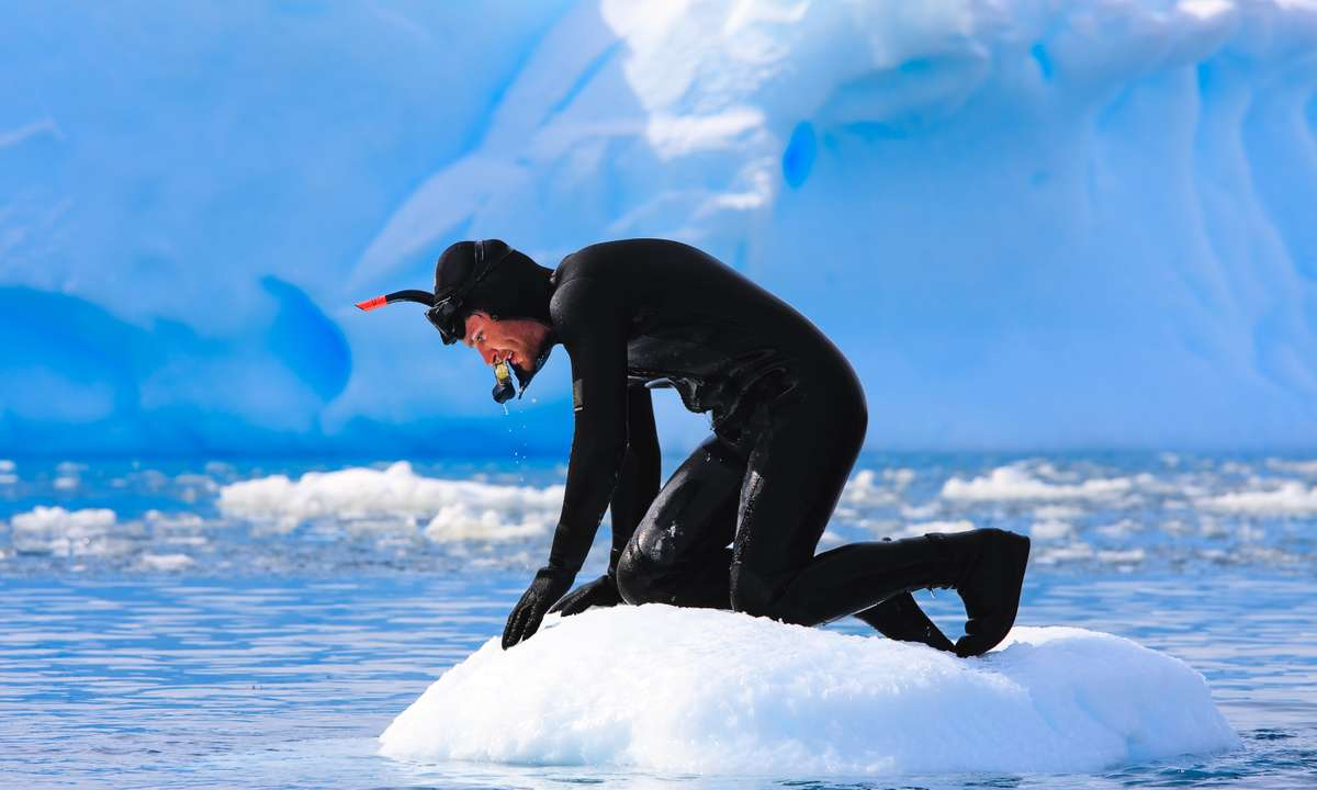 A diver on ice in Antarctica (Dreamstime)