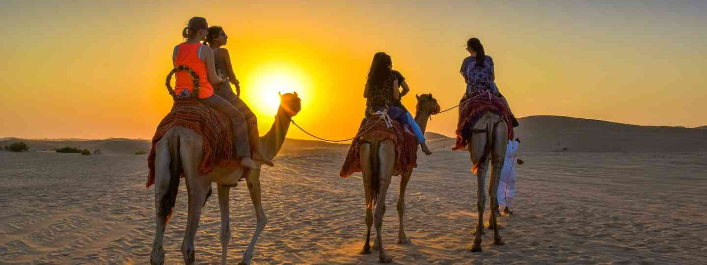 Family riding a camel at sunrise (Dreamstime)