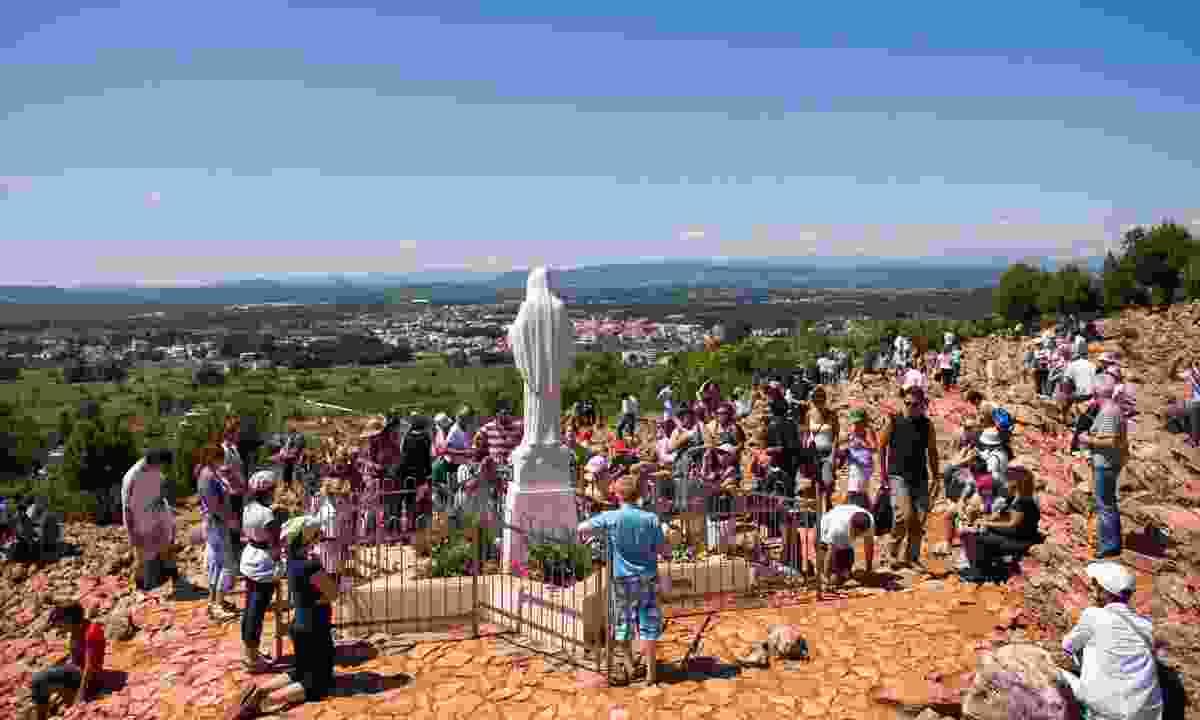 Pilgrims praying in front of Statue of Virgin Mary in Medjugorje  (Shutterstock)