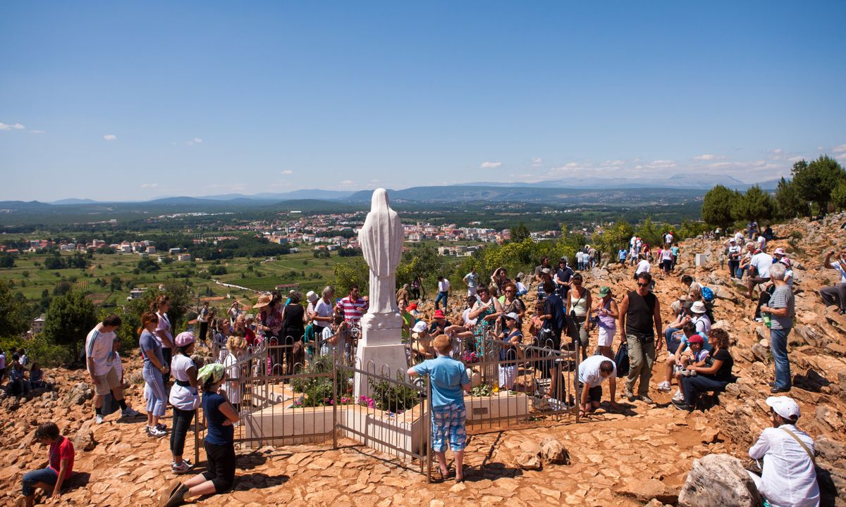 Pilgrims praying in front of Statue of Virgin Mary in Medjugorje (Shutterstock)