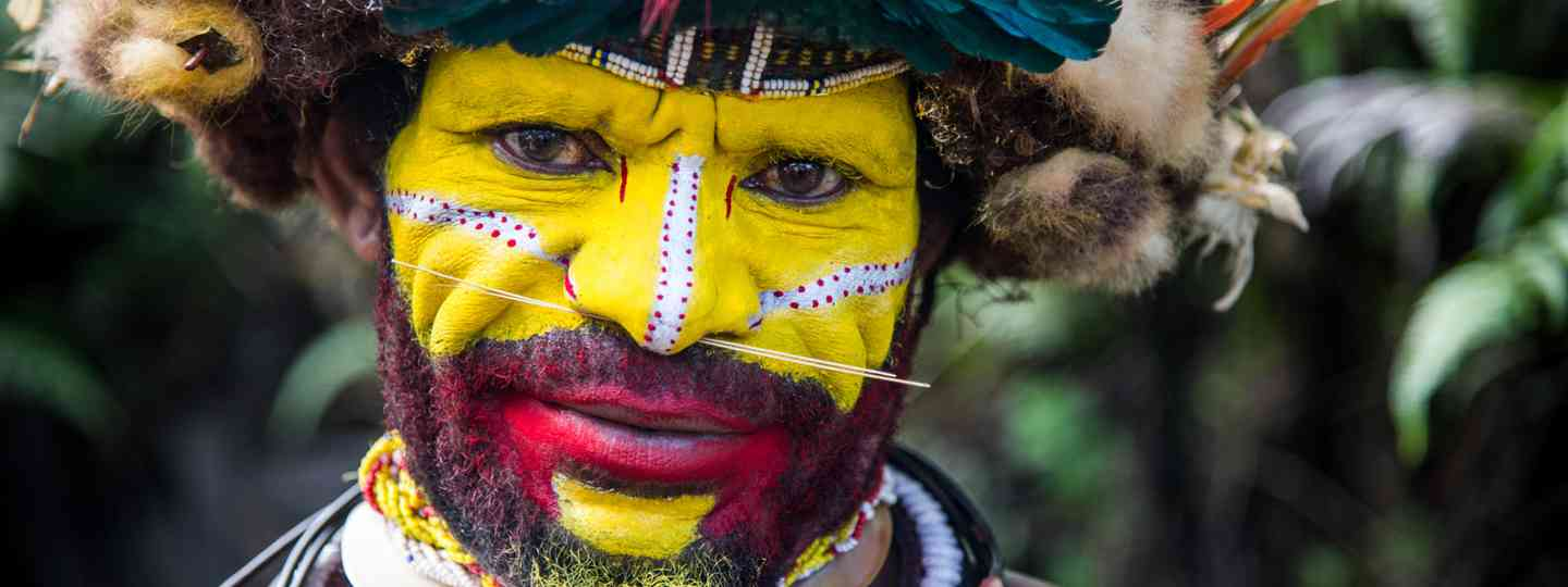 The Huli Wigmen have a fine bone driven through their noses and yellow painted faces (Dreamstime)