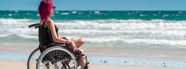 Wheelchair user looking out to sea (Dreamstime)