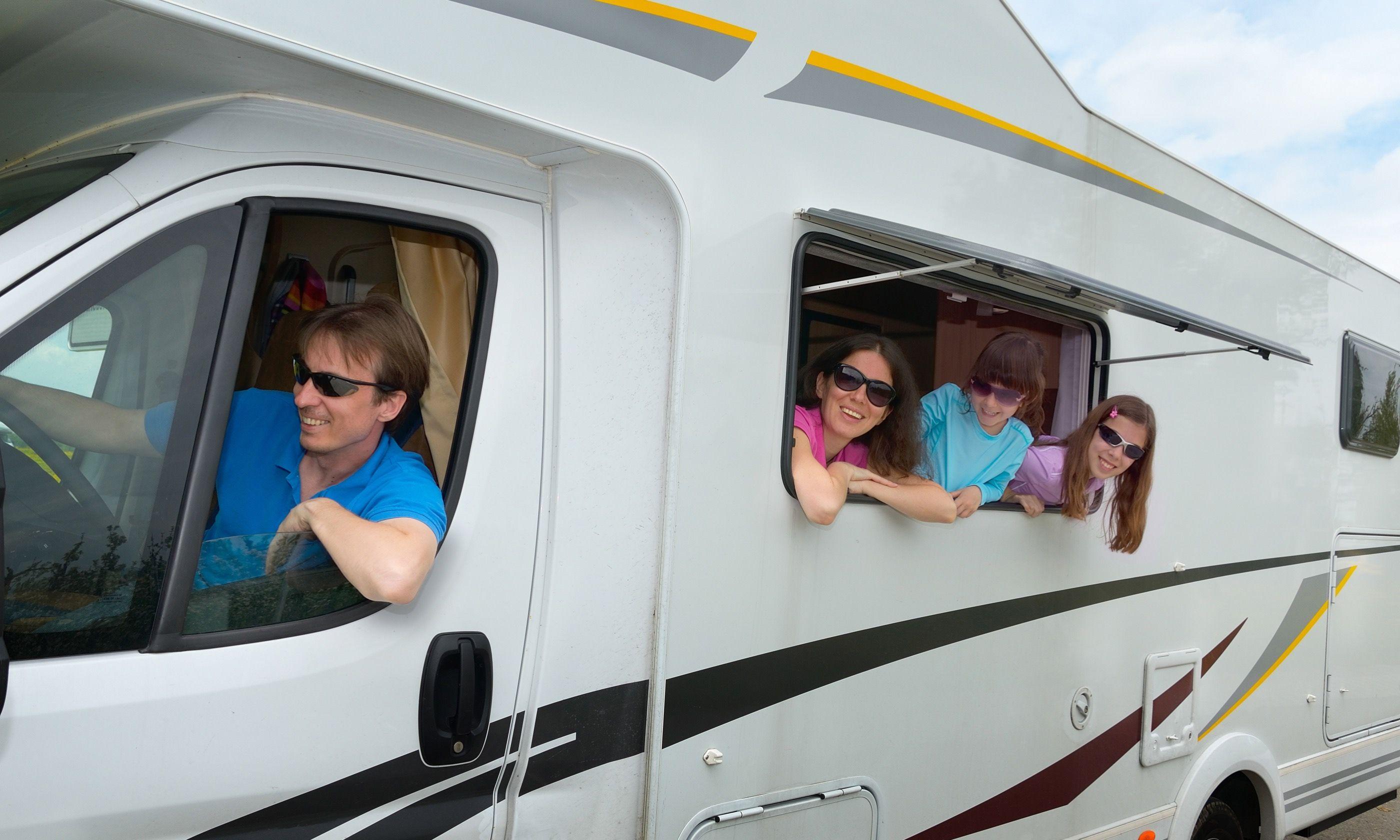 Kids hanging out of campervan (Shutterstock.com)
