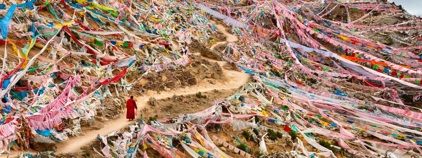 Monk walking through flag-covered mountainside in Tibet (Phil Borges)