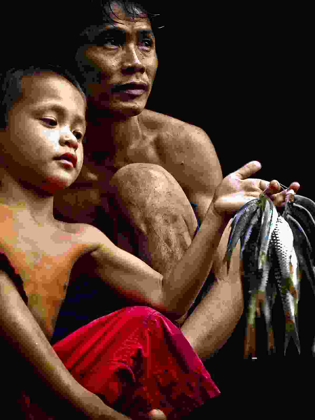 Penan father and son, counting their catch (Dreamstime)