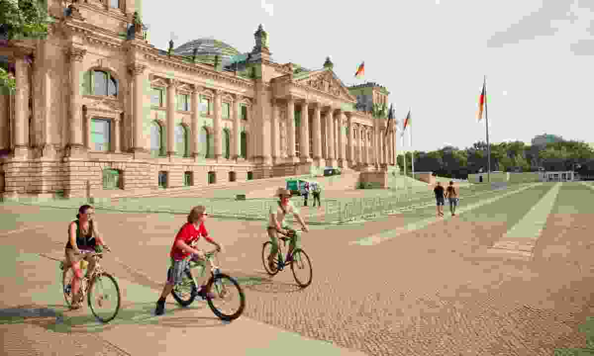 Family cycling around the Reichstag in Berlin (Dreamstime)
