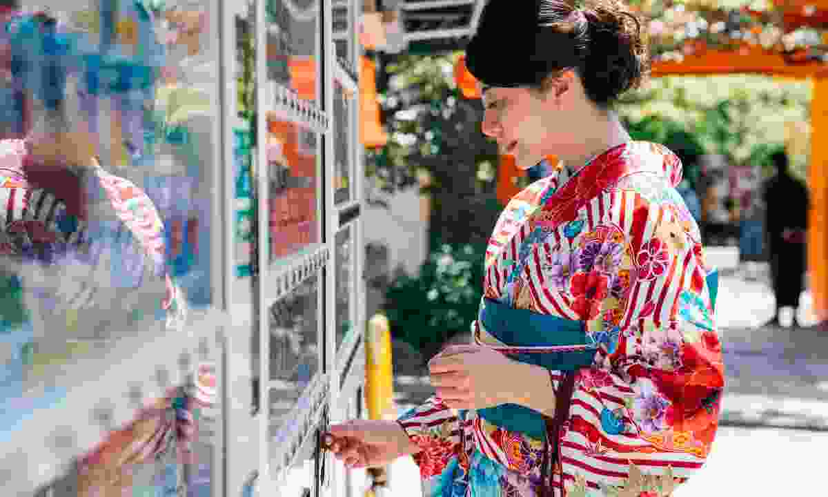 Geisha choosing a drink from vending machine in Kyoto, Japan (Shutterstock)