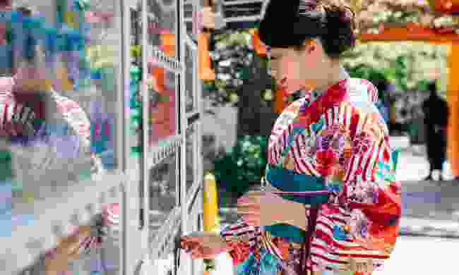 Geisha choosing a drink from vending machine in Kyoto, Japan (Shutterstock)