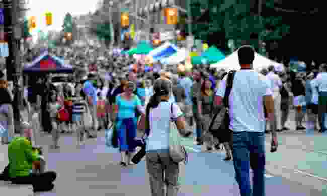 A couple walking into a crowded street festival  (Dreamstime)