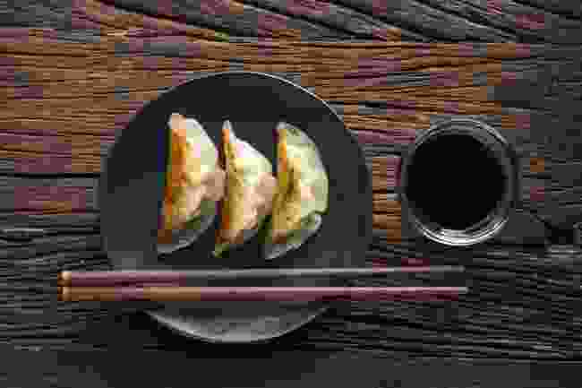 A plate of Japanese gyoza dumplings sitting on a rustic wooden table (Shutterstock)