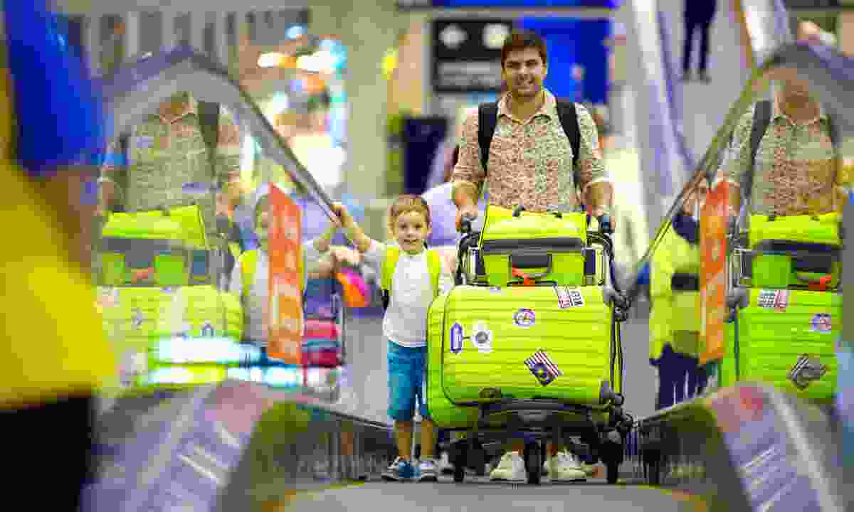 Family with baggage at airport (Dreamstime)