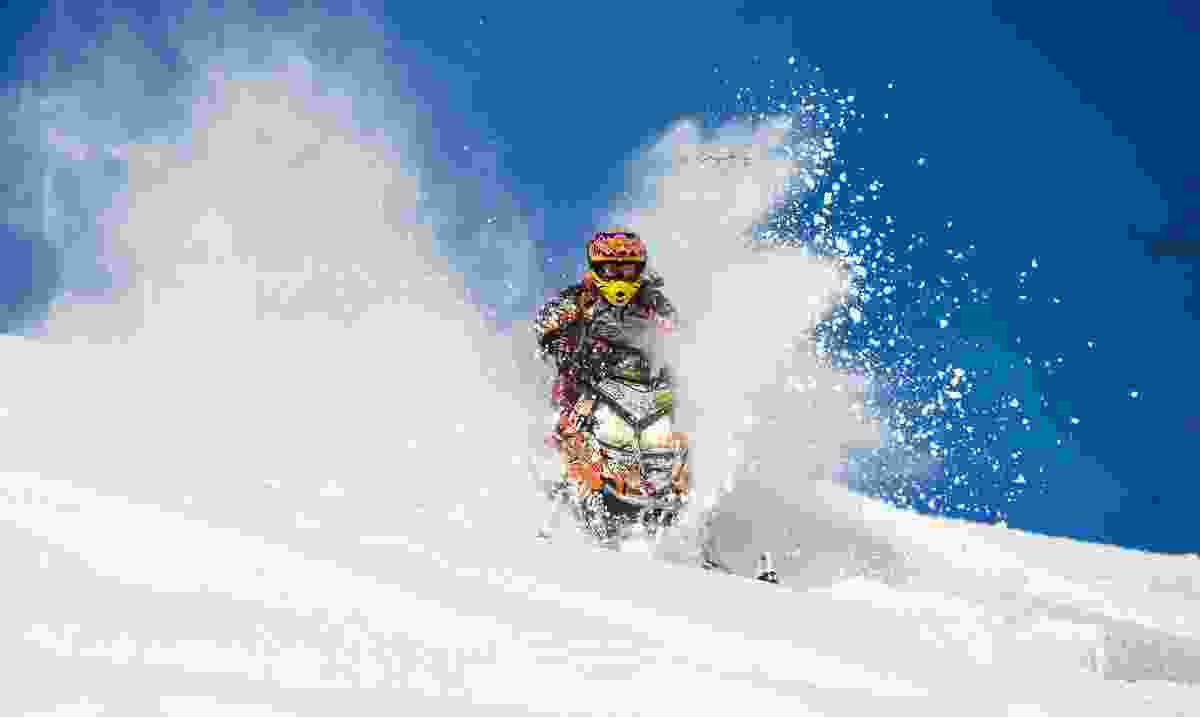 A man driving a snowmobile in the mountains (Dreamstime)