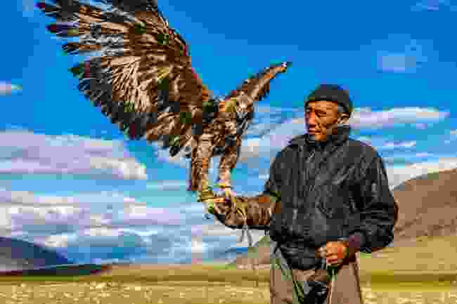 Khuanitkhan, one of the famous eagle hunters of the Mongolian Altai region, stands with his golden eagle (Marcus Westberg)