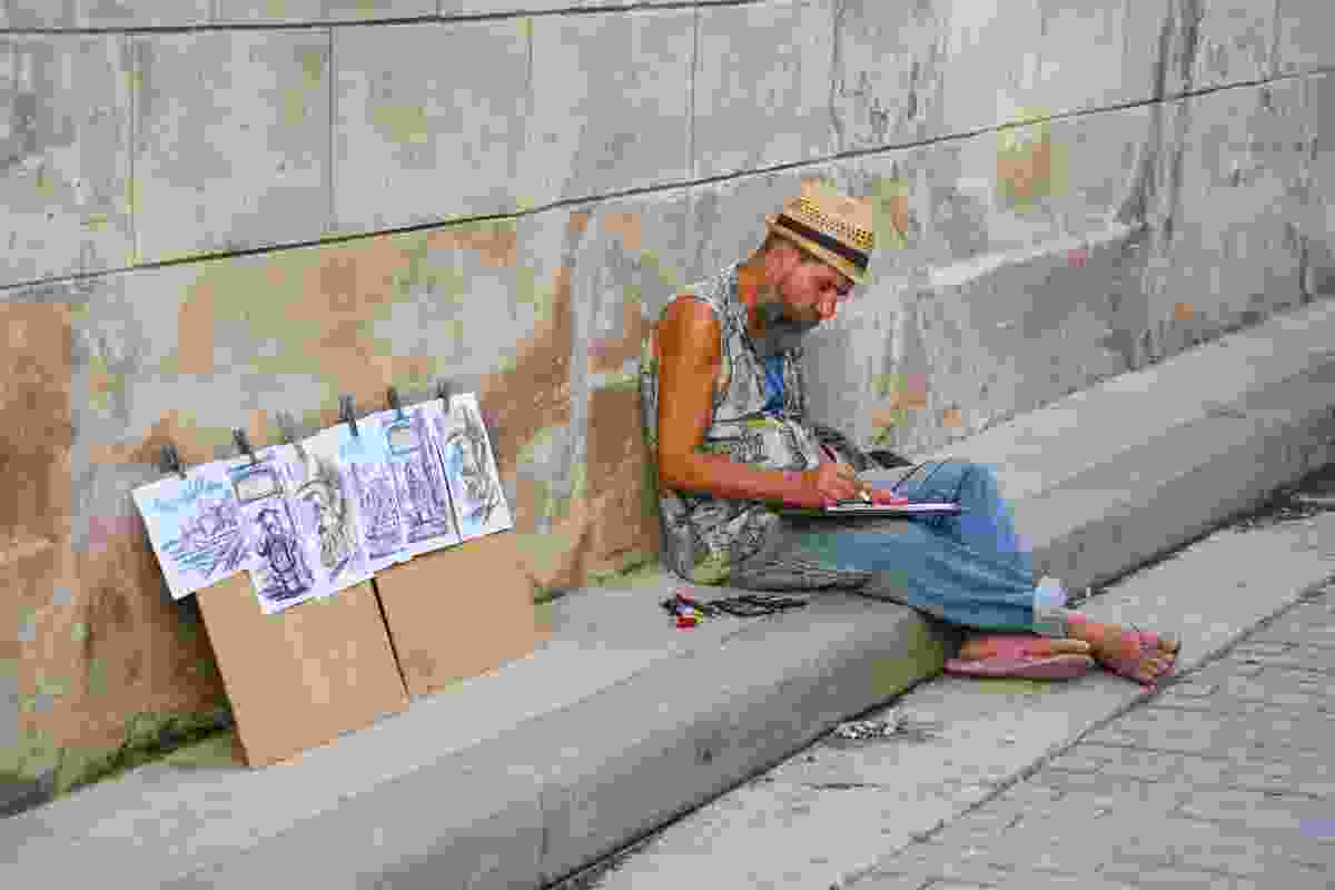 A local artist works on illustrations to sell to tourists on Empedrado (Graeme Green)