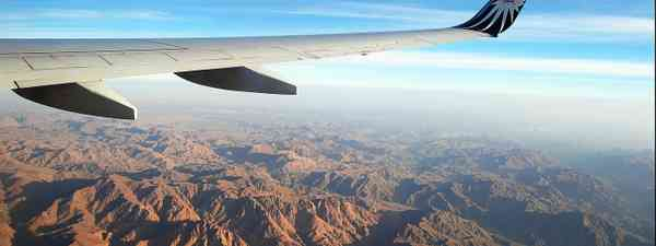 A plane flying over mountains (Dreamstime)