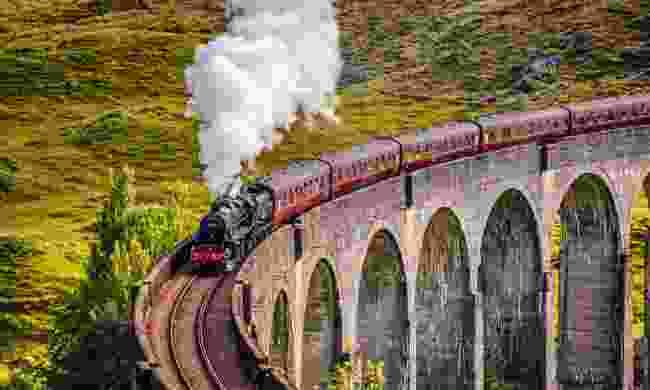 Steam train crossing the Glenfinnan Railway Viaduct (Dreamstime)