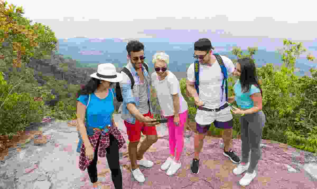 A group of tourists taking pictures from the top of a mountain (Dreamstime)