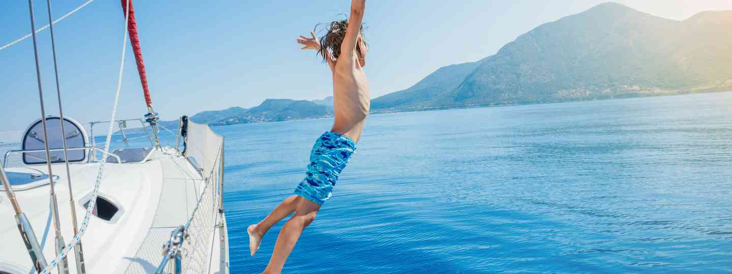 Boy jumping off yacht (Dreamstime)