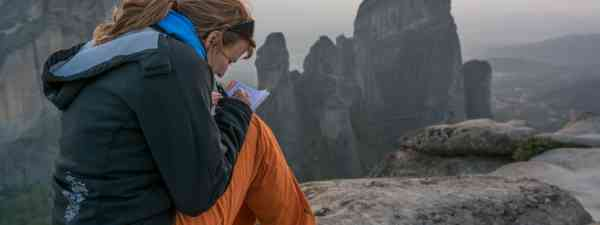 Travelling woman writes in her travel diary (Dreamstime)