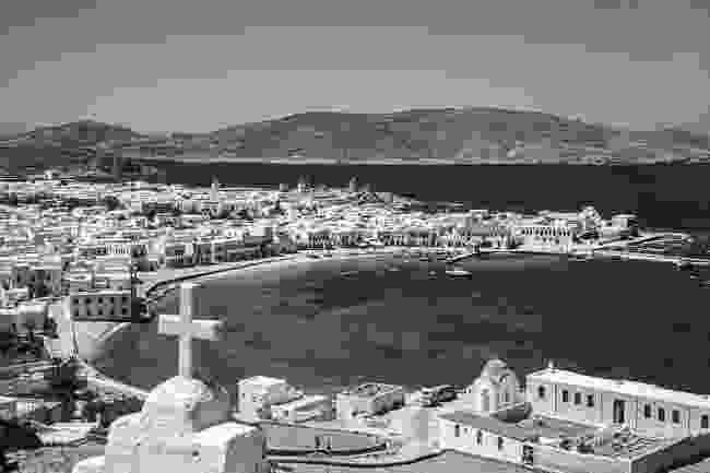 A view of Chora from the chapel of Saint Vassilis. On the bottom right is the Archaeological Museum and next to it is the chapel of The Rose that Never Withers, the Gryparis family church. The Old Port was one of the least protected harbors in the Aegean and was often severely damaged in storms (Robert A. McCabe)
