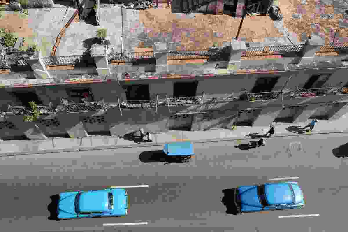 Balcony view looking down on road, busy with blue cars and a blue bike-taxi (Graeme Green)