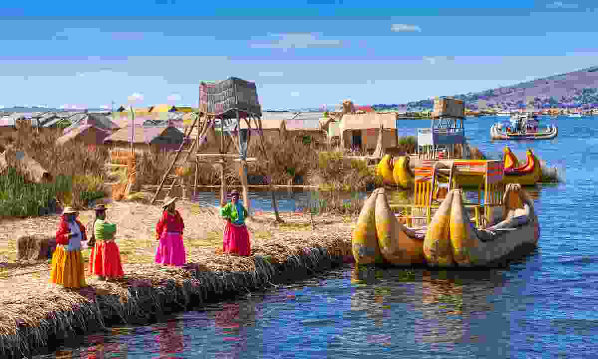 Women in traditional dresses welcome tourists in Uros Island (Shutterstock)