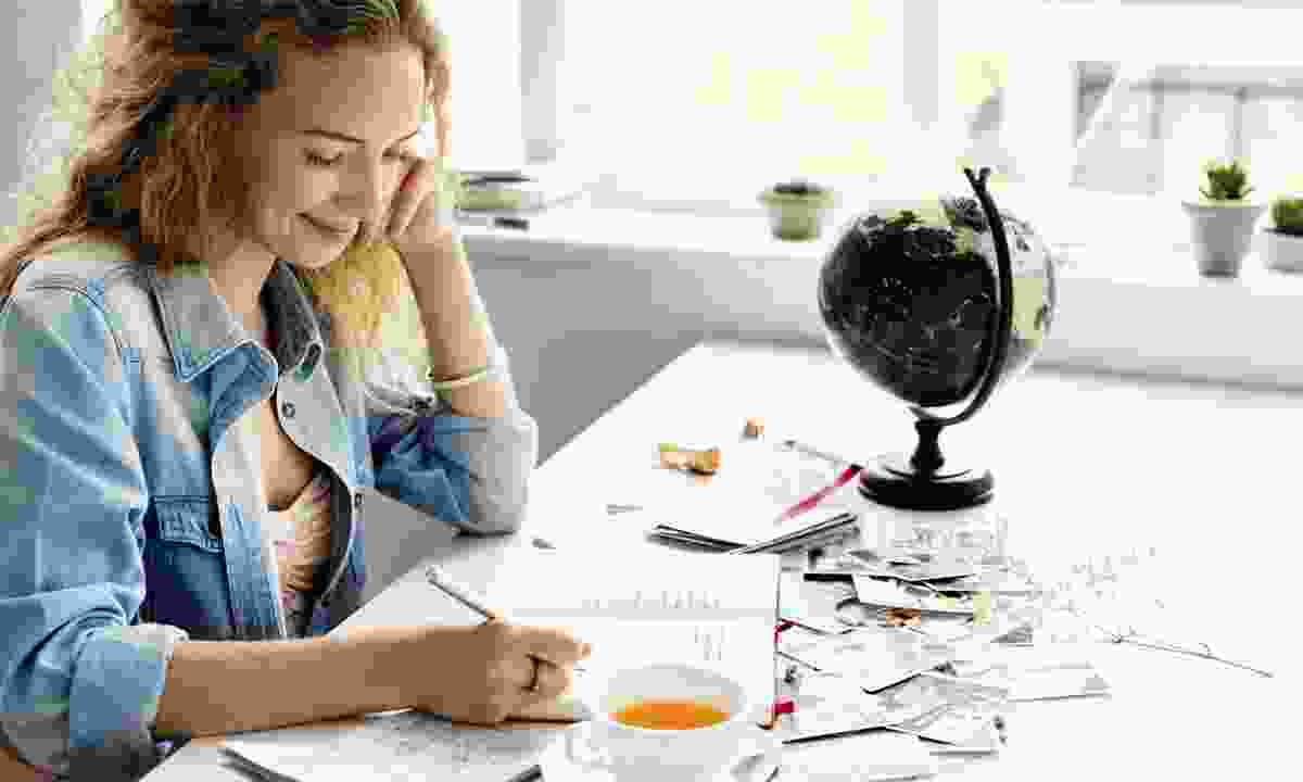 Woman writing in notebook (Dreamstime)