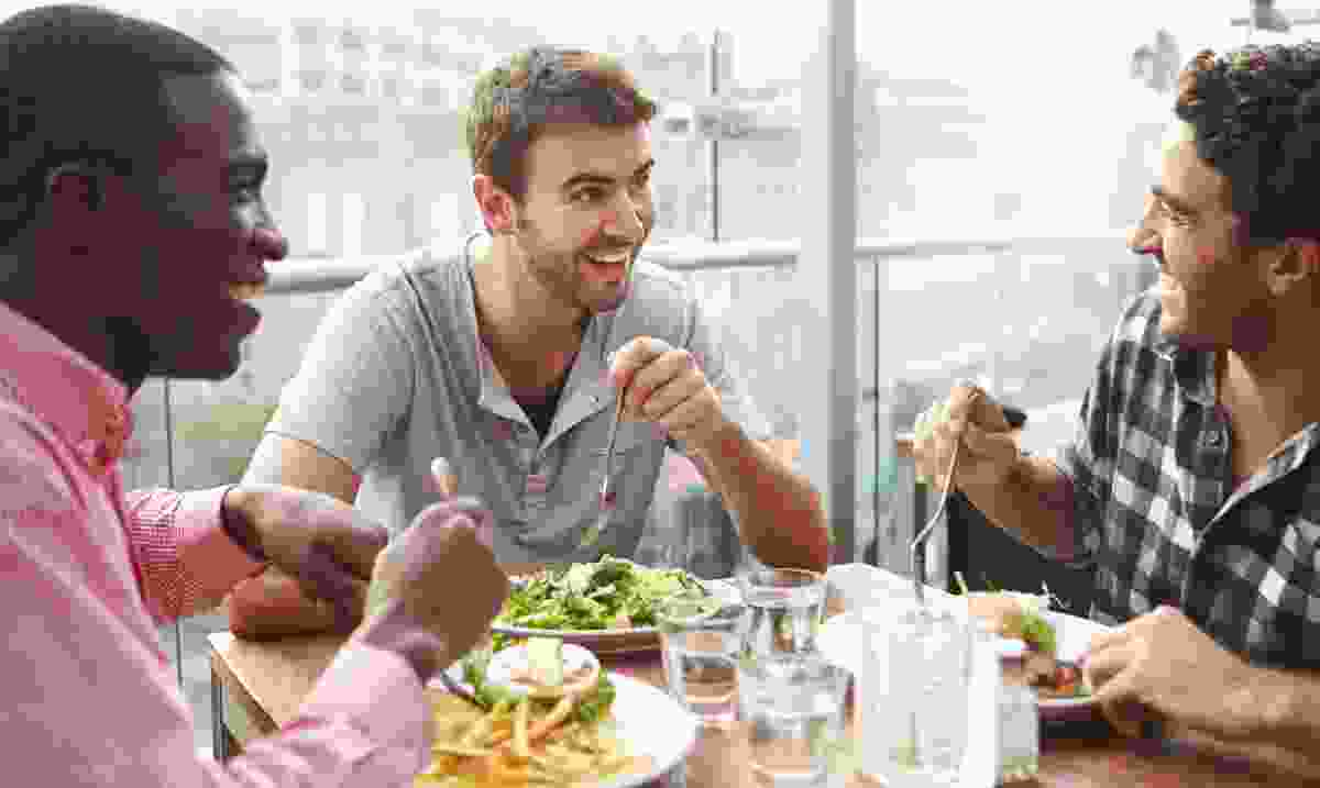 A group of men enjoying lunch at a rooftop restaurant (Dreamstime)