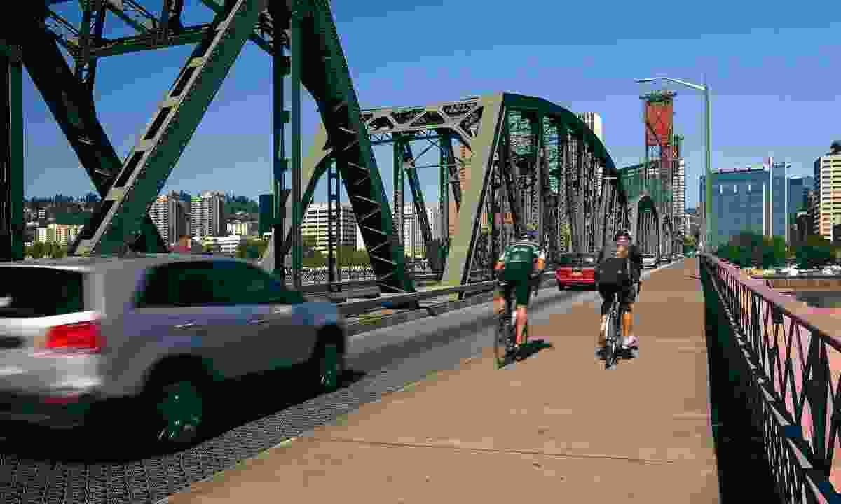Cyclists cross the Hawthorn bridge heading into Portland, Oregon (Dreamstime)