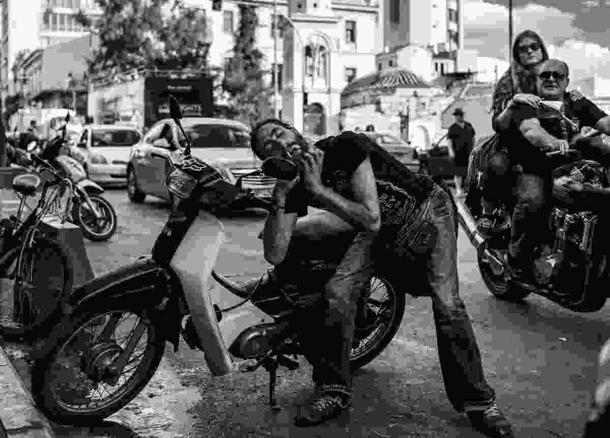 Motorcyclist grooming in his wing mirror, Athens (Derren Brown)