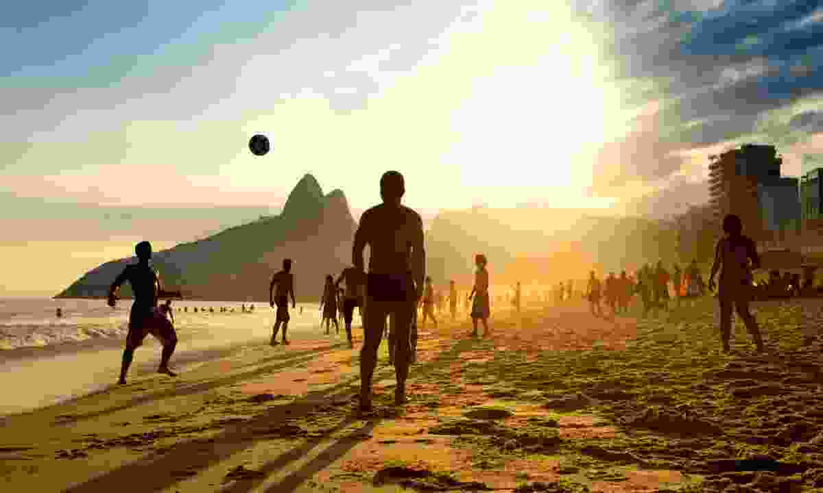 Boys playing football on Ipanema beach at sunset (Dreamstime)