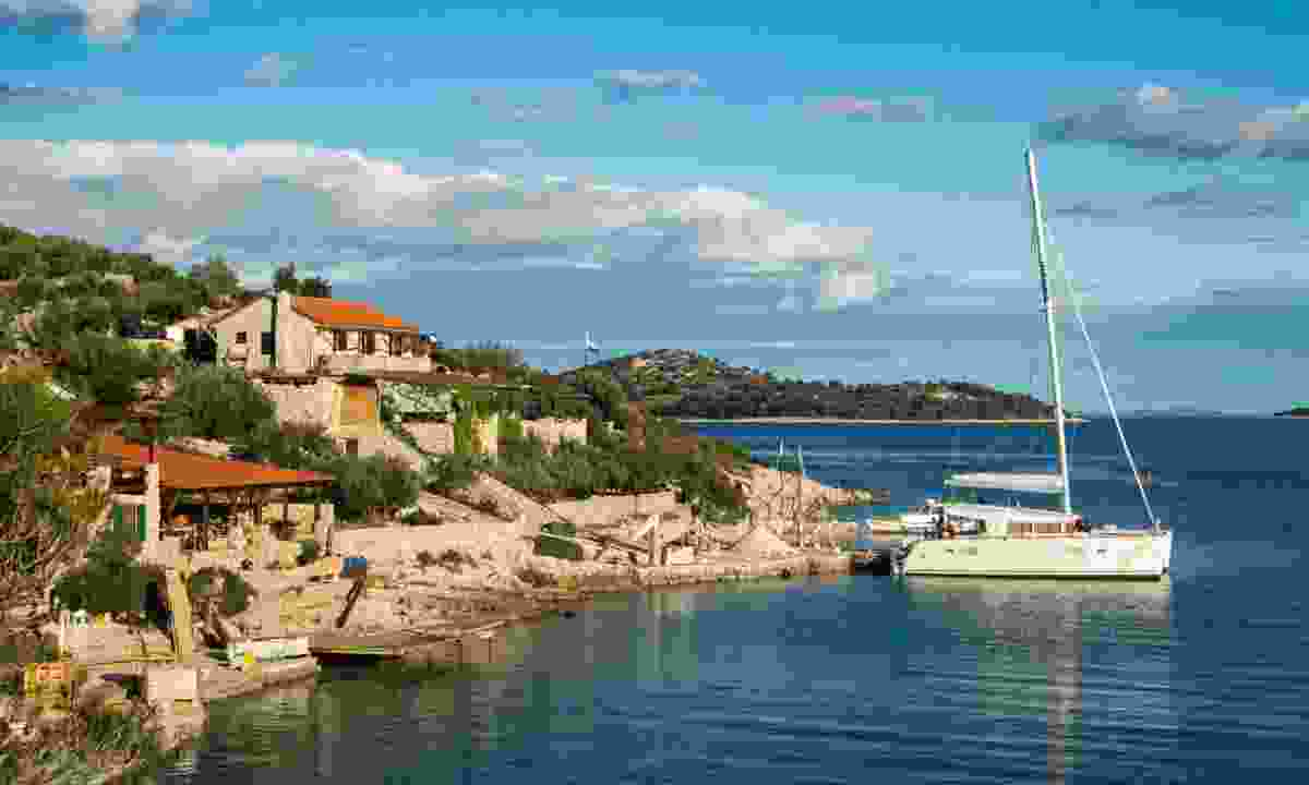 Catamaran docked in a bay with restaurant in Croatia (Dreamstime)