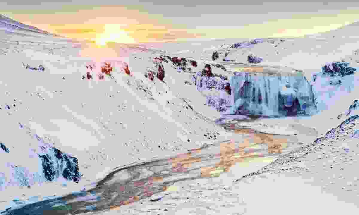 Sunrise over frozen waterfall in Iceland (Shutterstock)