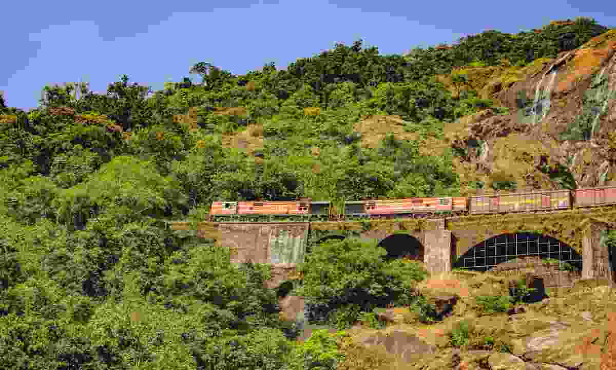 A train crosses the railroad bridge past Dudhsagar Waterfall (Dreamstime)