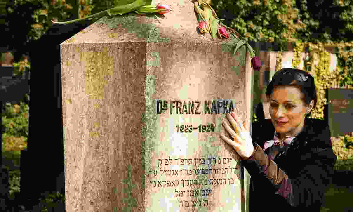 Woman paying respects at Franz Kafka's grave in Prague (Dreamstime)