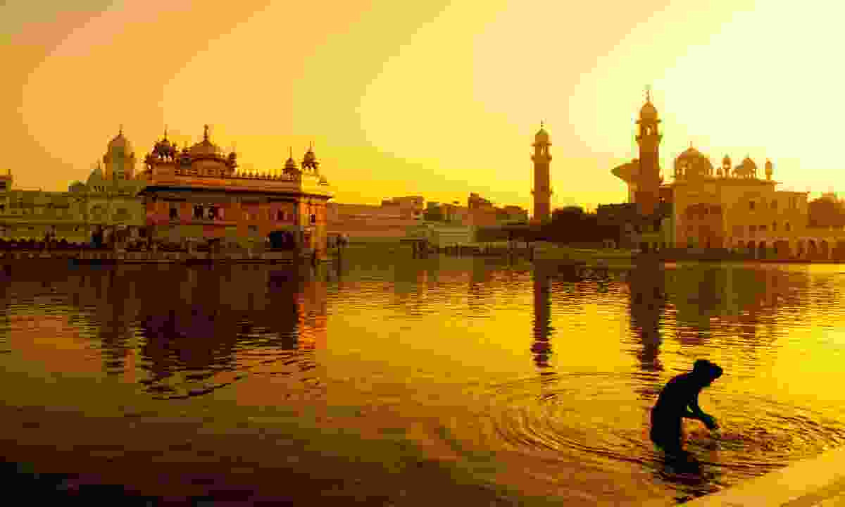 Pilgrim bathing in front of the Golden Temple (Dreamstime)