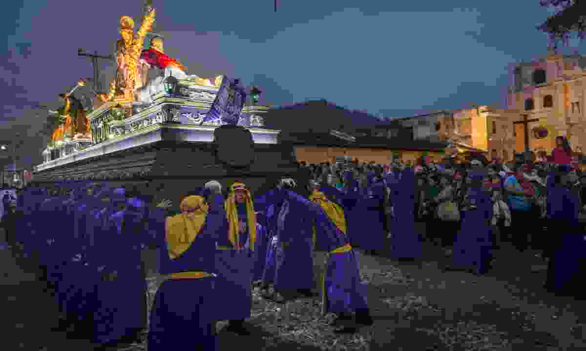 Penitents carrying a float with the image of Jesus Christ in an Easter procession at night during the Holy Week in Antigua, Guatemala (Dreamstime)