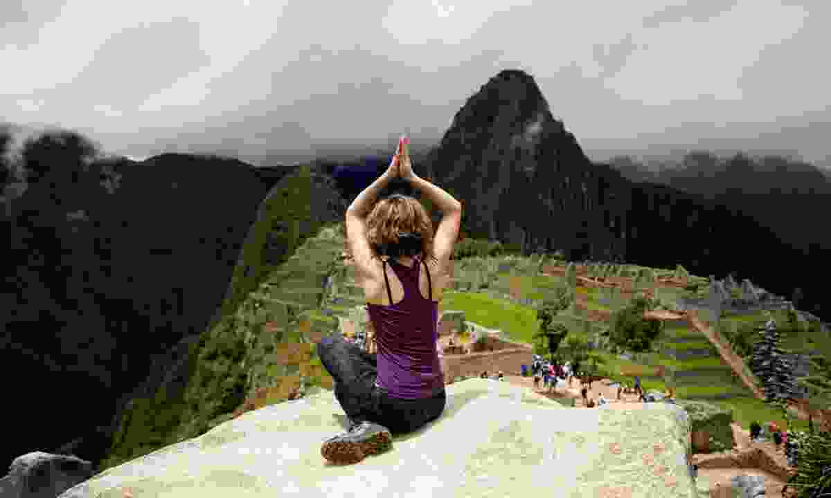 Woman meditating above Machu Picchu (Shutterstock)