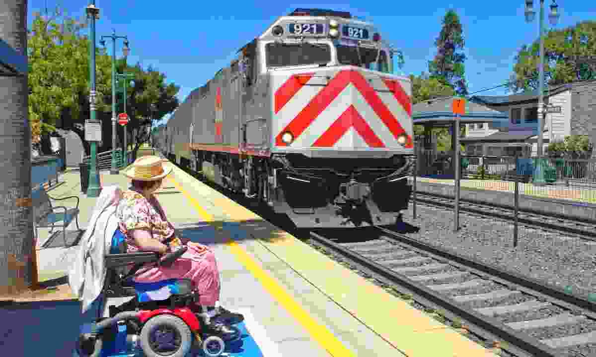 Woman in a wheelchair waiting in a station's assisted boarding area (Dreamstime)