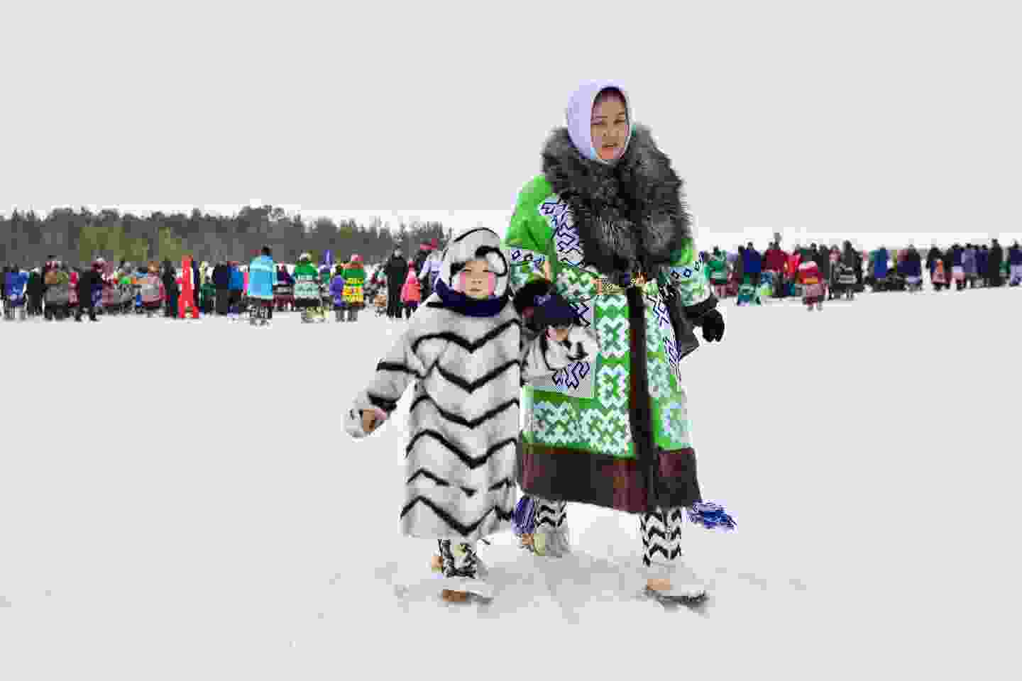 An ethnic Khanty woman with a boy, wearing traditional khanty winter coats at the Reindeer Herder Festival (Shutterstock)