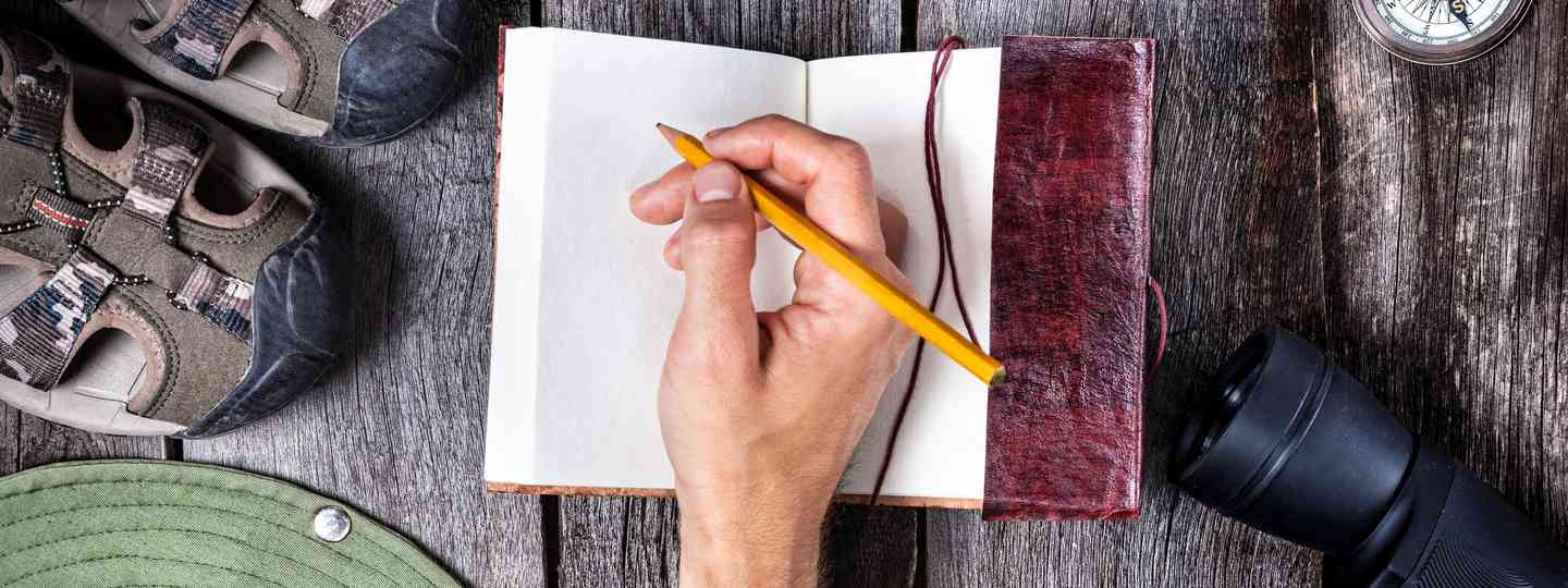 Travel writer with journal (Dreamstime)