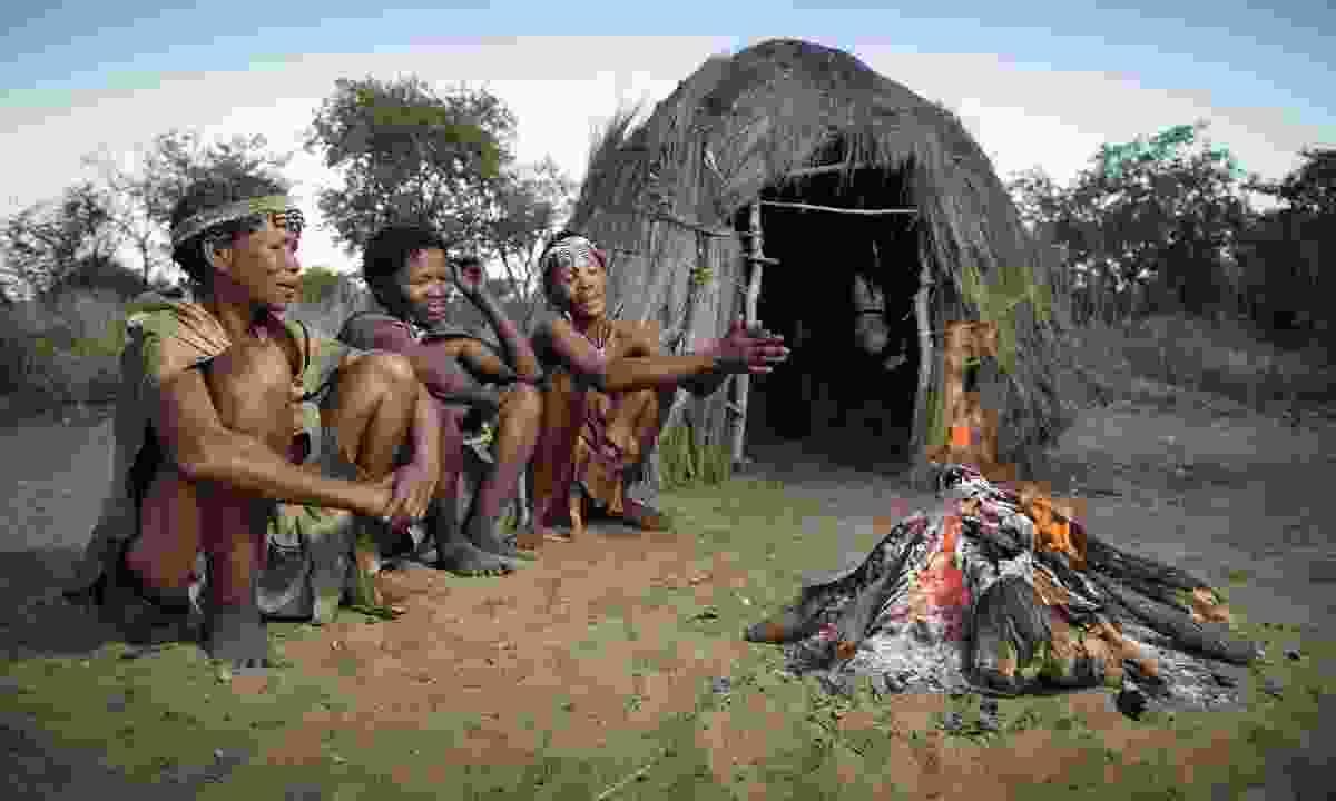 San Bushmen gather around a fire at dusk (Shutterstock)