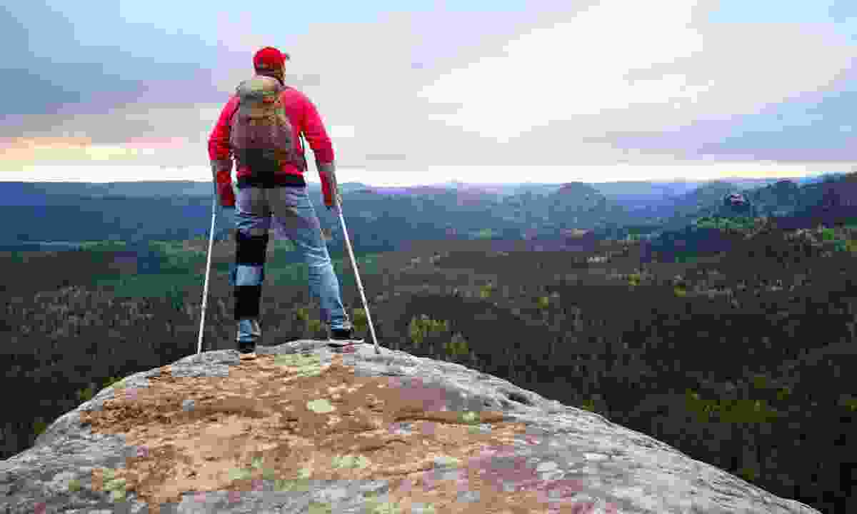 Man with crutches on a mountain summit (Dreamstime)