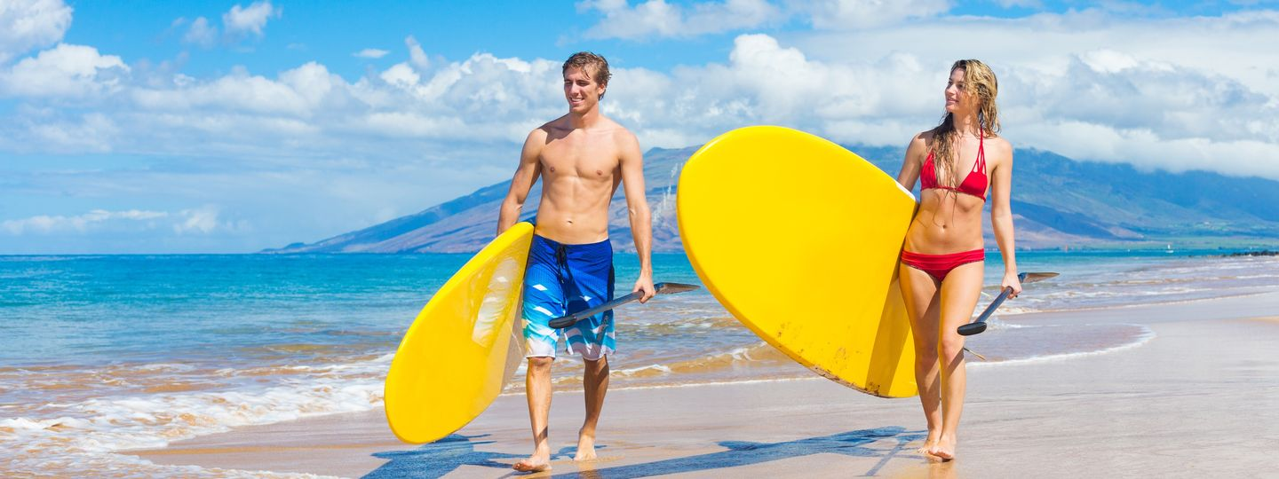 Couple paddleboarding in Hawaii (Dreamstime)