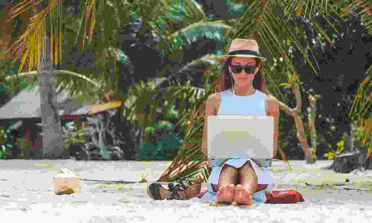 Girl writing on a tropical beach (Dreamstime)