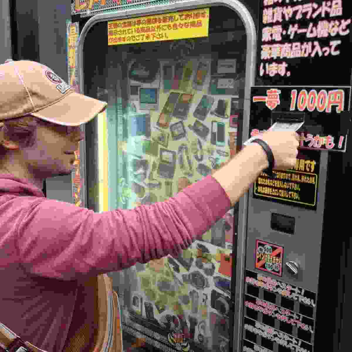 A tourist trying his luck on a lucky dip vending machine in Japan (Steve Parker)
